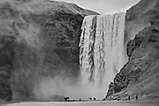 Sight seers are dwarfed by Skogafoss waterfall, Iceland (photographed in September 2013)