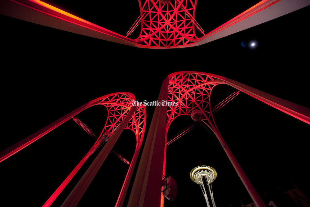 Looking a little like the tendons of heart valves, Pacific Science Center's arches bask in red light, with the Space Needle in the background.<br /> <br /> Ellen Banner / The Seattle Times