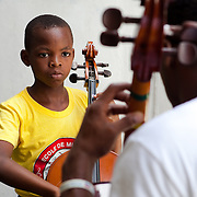 A cello student concentrates while learning hand placement. Dessaix Baptiste students show intense focus and a willingness to learn.