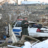 A police officer looks at his phone as he stands amid damage in Henryville, Indiana Friday afternoon after a tornado ripped through the town. One person was reported to be killed in the town..Chris Bergin/SWAT Chasers