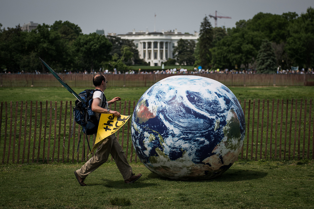 A man chases a runaway inflatable globe near the White House during the Climate March in Washington, D.C. on April 29, 2017. CREDIT: Mark Kauzlarich for CNN