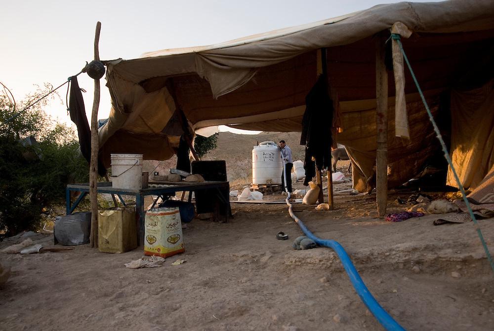 De tradition nomade, cette famille de Bédouins vit toujours sous des tentes mais s'est sédentarisée en bordure de agglomération de Pella. Sans accès à l'eau courante, chaque semaine ils se font livrer de l'eau qu'ils stockent dans des réservoirs, pour eux et pour leur troupeau de chèvres. Jordanie, mai 2011