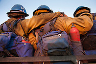 Texas Canyon Hotshots firefighters crowd into an available truck for a ride from the fire line to their staging site as they head to camp after the evening shift change.