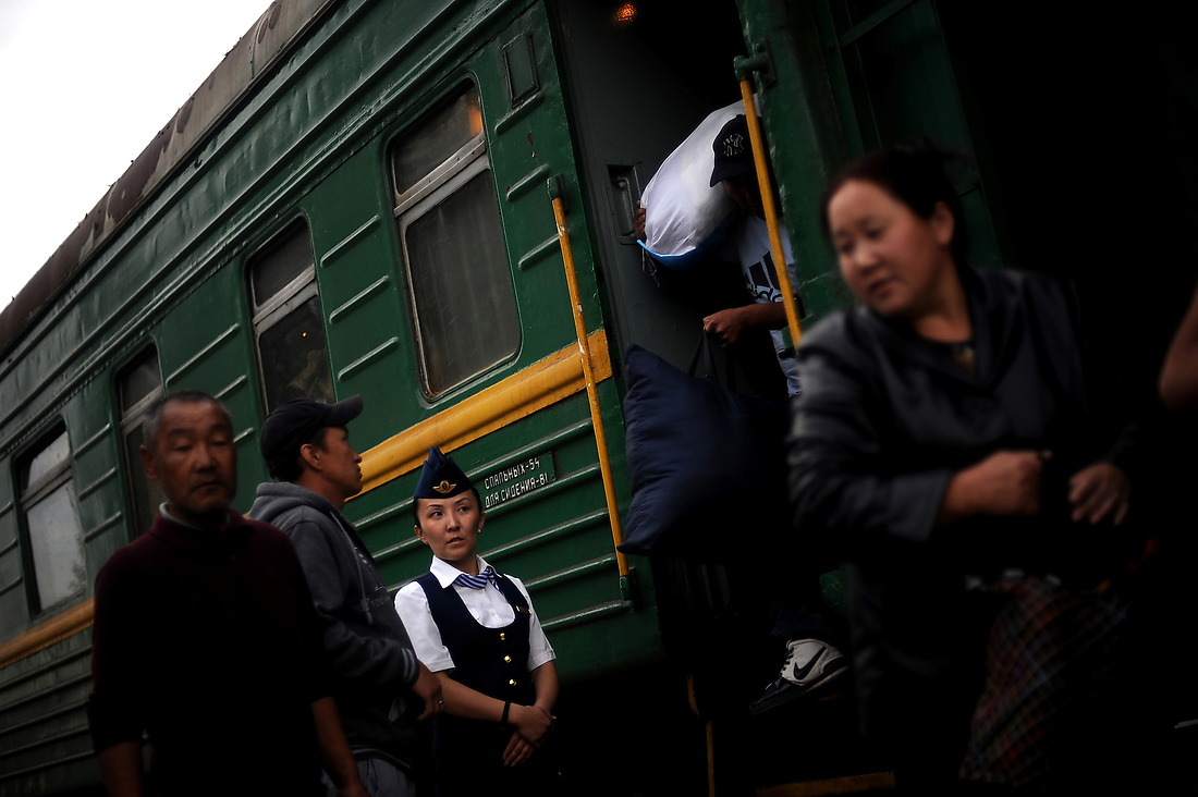 A Mongolian train attendant watches as the first train of the morning unloads its passengers at the Ulaanbaatar train station. Most of the early morning passengers are herders carrying milk containers and other goods from the countryside to sell on the streets in the city. — © Jeremy Lock/USAF
