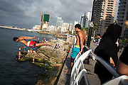 A man dives into the Mediterranean Sea from the Corniche, in Beirut, Lebanon. Beirut can seem a place apart from the rest of Lebanon and has, for the most part, remained calm as unrest grips other parts of the country.