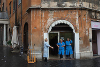 Women take a work break outside a shop in Rome, Italy
