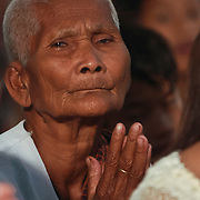 An older Cambodia woman offers prayers at a temple in Phnom Penh.