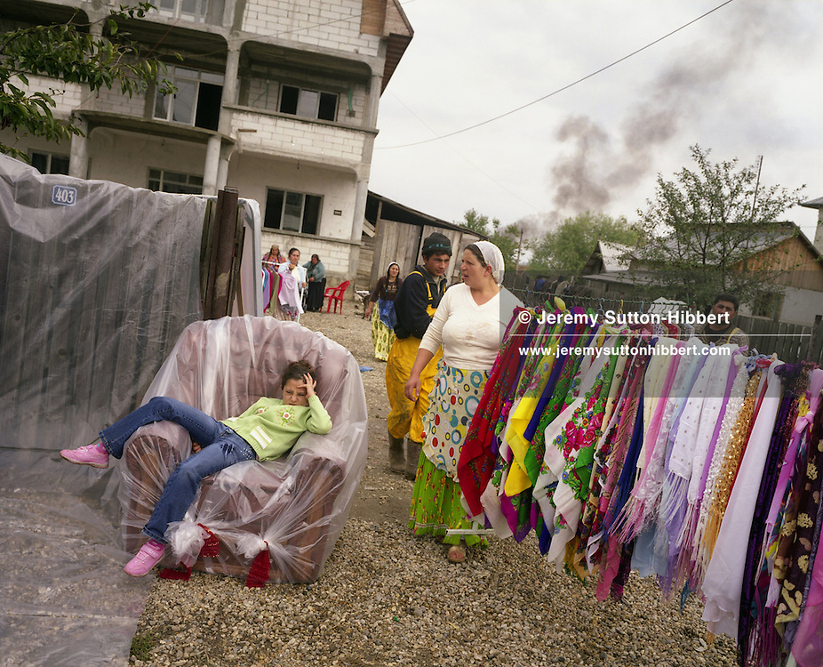 "Isabella Mihai sits bored on an armchair which is part of the dowry presents (along with the rack of scarves) of her elder sister Garoafa, on the day of Garoafa's wedding to Florin 'Ciprian' Lulu,  in the village of Sintesti, in Romania, Sunday, Sept. 24, 2006.  The dowry gifts are brought from Garoafa's family's home to be displayed along the roadside, for all the village to see. For the wedding 100 pigs, costing approximately 30,000 USD, were slaughtered. Garoafa wore a gold ""salbe""- a necklace of gold Franz Josef coins, worth an estimated 30,000 USD. The Kalderari roma of Sintesti are by tradition metal workers, originally making alcohol stills, pots and pans, but now dealing in scrap metal ( the smoke in the background comes from a metal furnace). The large profits from their business have enabled them to build large houses in the village of Sintesti, 20km from Bucharest, and to invest in fast, Western brand name cars such as BMW's, Mercedes and Porsche."