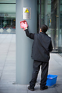 UK. London. Cleaning CCTV camera signs outside a London office building..Photo by Steve Forrest