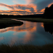 A stormy sunrise reflects in the Gibbon River, which cuts through the west side of Yellowstone National Park, Wyoming.