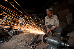 A picture made available on 31 May 2013 of a blacksmith of the Uighur  ethnic group working on iron wares in Kashgar, western edge of China's Xinjiang Uighur Autonomous Region, China 24 May 2013. Uighurs, a Muslim ethnic minority group in China, make up about 40 per cent of the 21.8 million people in Xinjiang, a vast, ethnically divided region that borders Pakistan, Afghanistan, Kazakhstan, Kyrgyzstan and Mongolia. Other ethnic minorities living in here include the Han Chinese, Kyrgyz, Mongolian and Tajiks people. In the restive region of Kashgar, western end of Xinjiang where the North and South Silk road meets, Uighurs comprise of more than 90 per cent of the 3.9 million population. Most practice a moderate form of Islam and religion is a major part of most ordinary Uighurs' lives. Tensions have been high between the Uighurs and the dominant Han Chinese as Uighurs complain of cultural and religious repression and claim that Han Chinese migrants enjoy the main benefits of development in the oil-rich but economically backward region.