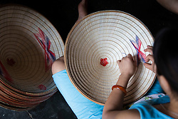 """Vietnamese artisans meticulously stitch conical hats, Chuong Village, Ha Tay Province, Vietnam, Southeast Asia, 2013. This handicraft village specializes in the fabrication of the conical hat, known as """"non"""" in Vietnamese."""