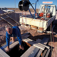 Australia, South Australia, (MR) Stuart Bird peers into 100' deep opal mine shaft in Coober Pedy.