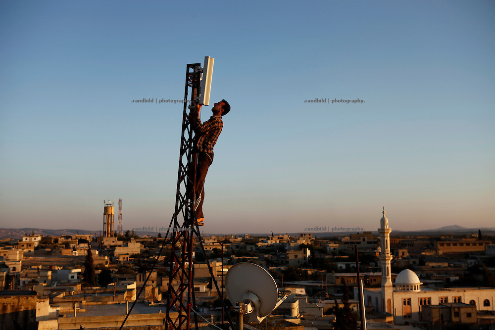 Mohammad, operator of the recently established Wi-Fi network covering Koreen, climbs up a transmission mast on a rooftop. It is the first time the village gets access to the world wide web at all. In the meantime another operater has set up a second network. Economic competition in times of uncertainty.<br /> <br /> <br /> <br />  _ _ _ <br /> <br /> <br /> <br /> Idlib Interim - Challenging life without central government in the village of Koreen (Idlib Province, Syria)<br /> <br /> <br /> <br /> Koreen joint the syrian uprisung to ouster president Bashar al-Assad at a very early stage in 2011. It has been scene of Army attacks and heavy shelling since 2012. In the course of the fightings the village of a few thousend inhabitants was almost abandoned as barrel bomb campaings commited by the regime pounded Koreen. But since regime forces retreated to few bases remaining in Idlib province people returned home to establish a new udn almost unregulated economic, social and community life. The regimes power has no affect anymore on them - a new government is not established yet and not in sight at all. Koreen is free to make its way.