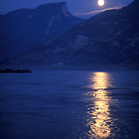 China, Sichuan Province, Fengjie, Full moon rises above hills along Yangtze River at dusk on autumn evening