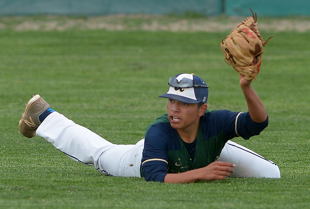 gbs041117q/SPORTS -- Artisco Heritage right fielder David Rodriguez holds up his glove after a diving catch of Albuquerque High's Graham Glasgow hit in the forth inning of the game at Albuquerque High on Tuesday, April 11, 2017.(Greg Sorber/Albuquerque Journal)