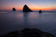 Several large sea stacks off Silver Point on the Oregon coast near Cannon Beach are surrounded by Pacific Ocean waves at twilight. The large sea stack on the left side of the image is known as the Jockey Cap.