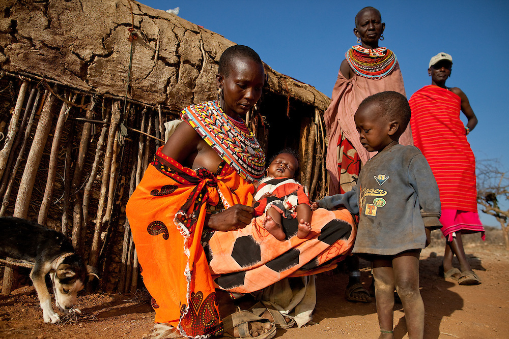 A Samburu family plus dog outside of their hut in northern Kenya
