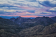 Photo by Leandra Lewis of winter sunset from Sky Island viewpoint highlighting the geology of the terrain and the pink cloudy sky over Tucson, AZ.