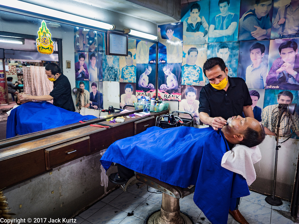 "06 FEBRUARY 2017 - BANGKOK, THAILAND: A mirror reflects a barber cutting a customer's hair in a small barbershop in what used to be known as Kalabok Market under the Phra Khanong Bridge in the Phra Khanong district of Bangkok. Kalabok is the Thai word for hairdresser and the market was called Kalabok because there were many barbershops and hairdressers under the bridge. In 1985, the city changed the name of the market to ""Singha Market."" There are still about 10 small men's barbershops, most with just one barber, and four women's salons, most with one hairdresser,  under the bridge.      PHOTO BY JACK KURTZ"