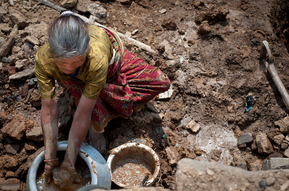 Woman mixes mud that she will later spread by hand over wooden slats to form walls. When complete, this will be her home.
