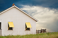 Beach house with yellow shutters and an approaching storm.