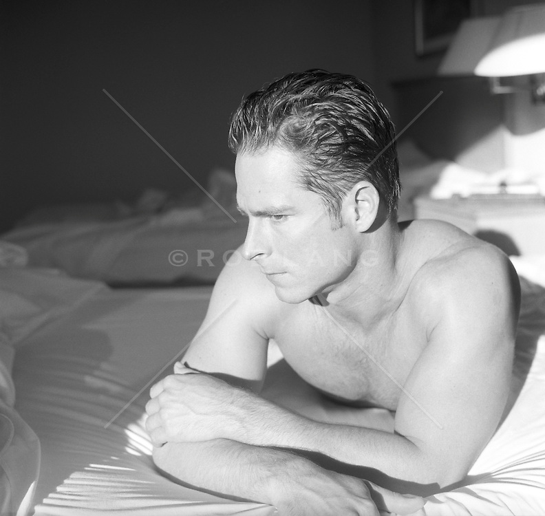 good looking man with slicked hair in bed