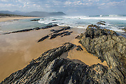 Intertidal rock pools on the edge of the sandy Natures Valley beach, Natures Valley, Western Cape, South Africa