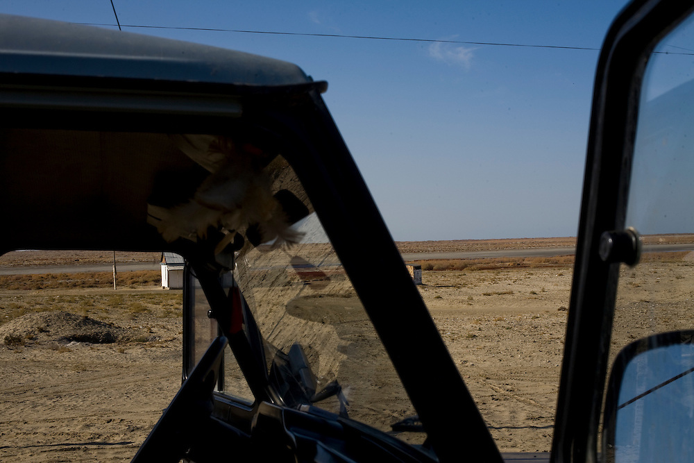 CREDIT: DOMINIC BRACCO II..SLUG:PRJ/KAZAKHSTAN..DATE: 11/30/2009..CAPTION:View through a Russian Jeep window near Aralsk...Aral Sea Overview: ..During the 1960s the USSR began irrigating the waters of the Aral Sea in southern Kazakhstan to combat their growing food crisis. The Soviets severely miscalculated and water began receding quickly from the port cities. The waters continued to recede. By 2000 the water was 80 km away from the city of Aralsk, a main seaport in Kazakhstan. In 2005 with help from the World Bank, construction began on a 13km dike that locals hoped would bring the waters back to their original shores. The project raised water quality and fishing was able to resume, however four years after completion of the dike the water is still 50km from Aralsk's port. Locals seem mixed on the possibility of the sea returning after more than 40 years without the sea. Fishermen from Aralsk make a three-hour path through soft desert road along the former seabed. The only source of income for many is cattle, horses, and camels, which have, began to overgraze the areas of the former seabed and surrounding desert. Because of this nutrient rich topsoil is lifted by the wind and the process of desertification continues.  .