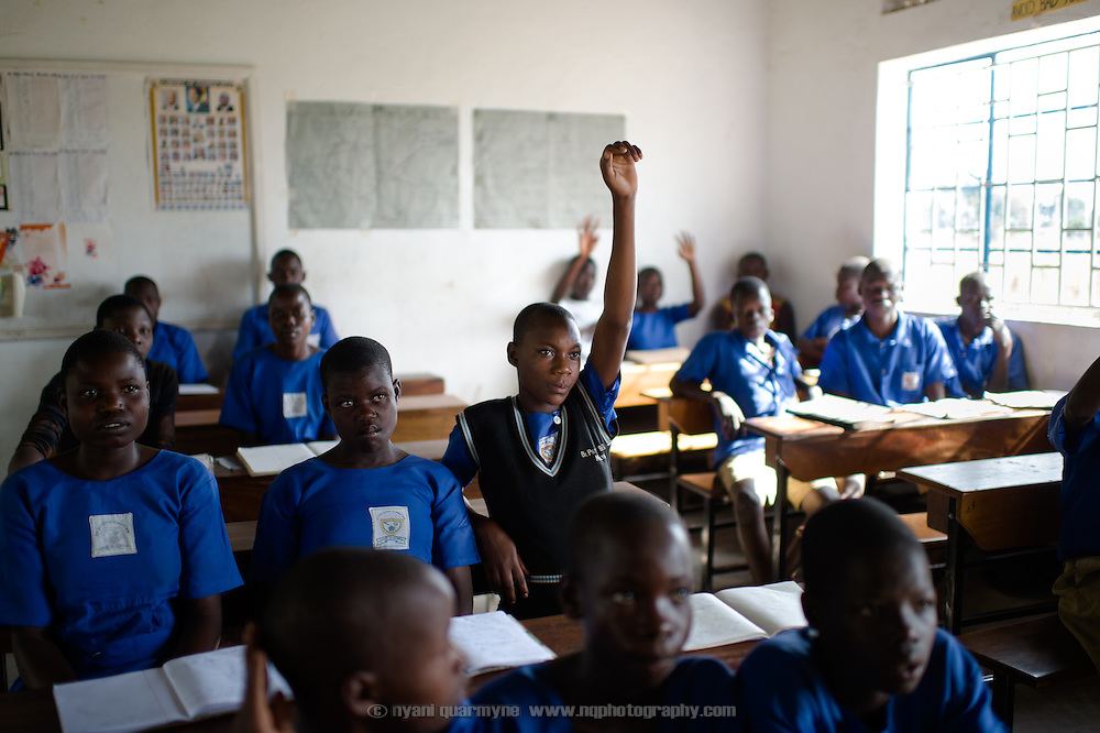 A girl raises her hand to answer a question during a presentation on Menstrual Hygiene Management at Agwait Primary School near Tororo in Eastern Uganda on 1 August 2014.