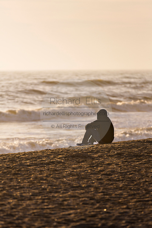 A lone person sits on the beach at sunrise on St Augustine Beach, Florida.