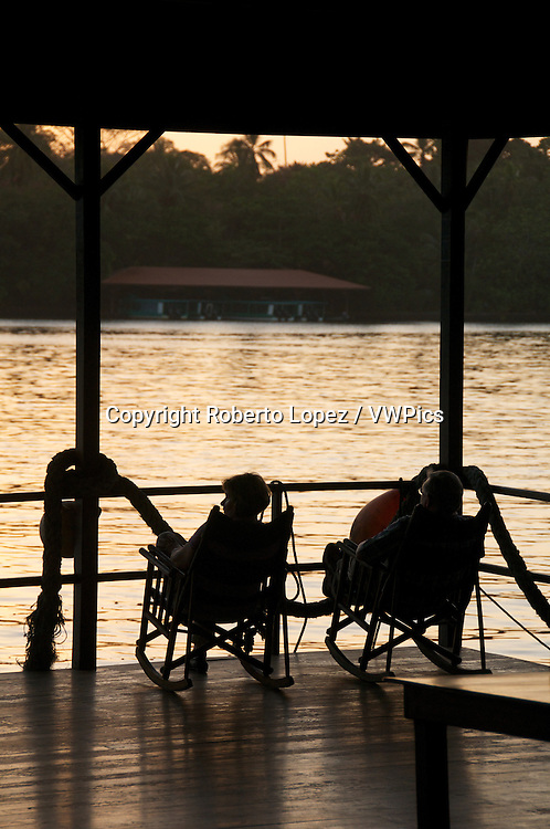 Two people admiring the view of the reflection of the sun at the Tortuguero River in Limon, Costa Rica.