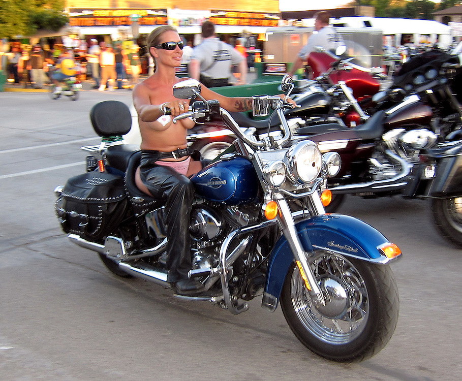 STURGIS, SOUTH DAKOTA - AUGUST 2010:  A female motorcyclist rides down Main Street in downtown Sturgis, South Dakota during the 70th annual Sturgis Motorcycle Rally held in the Black Hills.  The attendance estimates were placed between 500, 000 and 700,000 bikers.