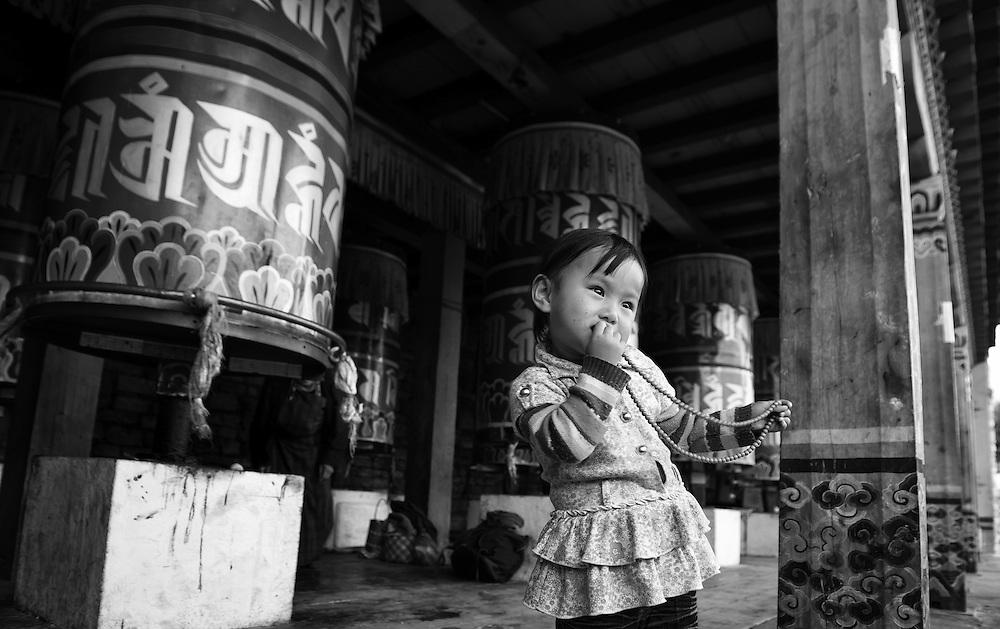 A young girl near the prayer wheels in a temple in Thimphu, Bhutan.