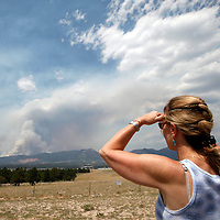 A woman watches as the city of Colorado Springs, Colorado is in the path of the Waldo Canyon wildfire burning in the mountains west of the city June 24, 2012.  Firefighters in Western U.S. states struggled to contain out-of-control wind-stoked wildfires across the U.S. west as summer temperatures mounted, and a fresh blaze consumed more homes in Colorado.  REUTERS/Rick Wilking (UNITED STATES)