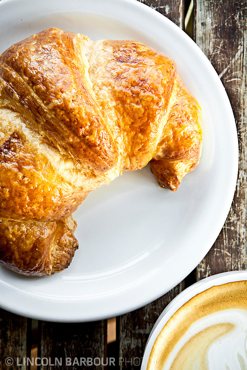 Overhead shot of a croissant and a latte on a white plate