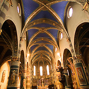 Interior of the Cathedral Donato of Pinerolo, in the Province of Torino, Turin, Piemonte (Piedmont), Italy. The church was built in the XIVth century by Pietro da Milano. Gothic structure in Baroque style. Dark blue painted arched ceiling,  religious iconic frescoes painted on church columns, round windows along ceiling, three arched windows behind pulpit are some of the highlights of this beautiful structure.