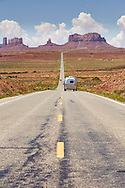An RV camp trailer drives down US Highway 163 leading south to the iconic sandstone buttes of Monument Valley, Arizona.