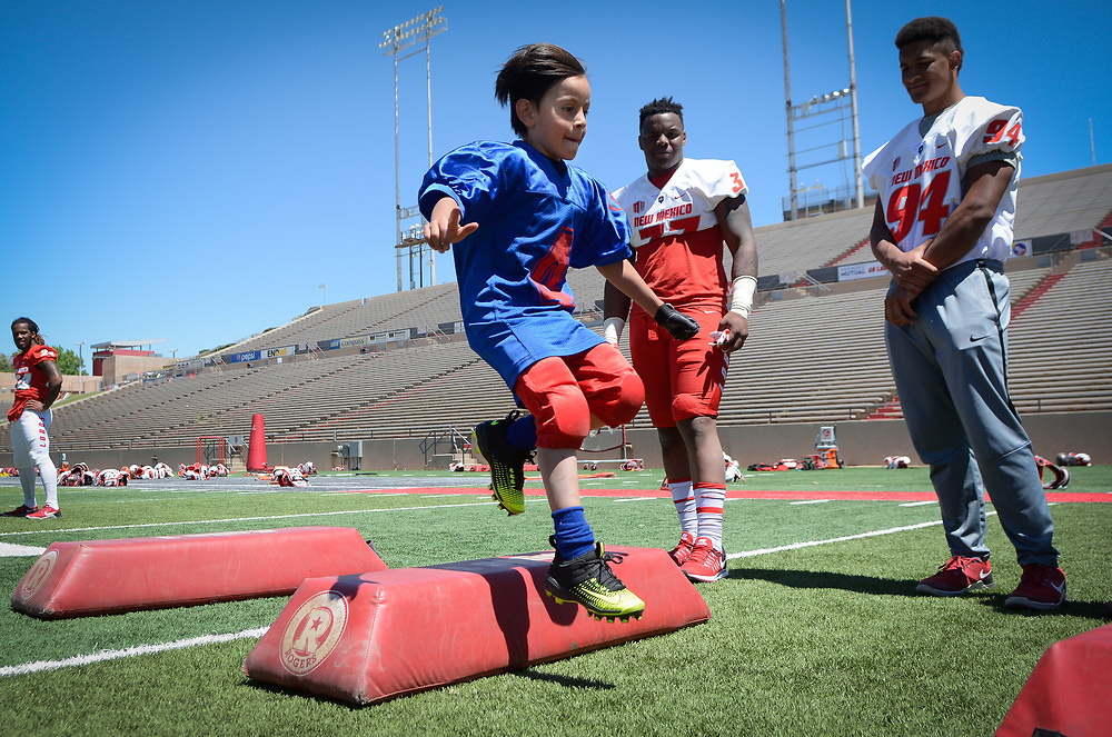 mkb042217f/metro/Marla Brose --  Azriel Romero leaps over a bag during he and other kids ran football drills with the University of New Mexico football players after their Spring Showcase, the final workout of the spring in University Stadium in Albuquerque, N.M., Saturday, April 22, 2017. (Marla Brose/Albuquerque Journal)