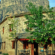 """Stay in a pension under the impressive Tymfi Massif, in Vikos village, Zagoria, north Pindus Mountains (Pindos or Pindhos), Epirus/Epiros, Greece, Europe. The northeast wall of Vikos Gorge is Mount Tymfi (or Greek: , also transliterated Timfi, Tymphe, or Tymphi), near the 40 degree parallel. Tymfi forms a massif with its highest peak, Gamila, at 2497 meters (8192 feet), the sixth highest in Greece. Vikos Gorge in northern Greece is the world's deepest canyon in proportion to its width, and at one point measures 2950 feet (900 meters) deep and 3600 feet (1100 meters) wide from rim to rim. Its depth is an impressive 82% of its width at that cross-section (depth/width ratio=0.82). Gorges in many countries have higher depth/width ratio, but none are as deep. Zagori (Greek: ) is a region and a municipality in the Pindus mountains in Epirus, in northwestern Greece. Zagori contains 45 villages collectively known as Zagoria (Zagorochoria or Zagorohoria). Published in """"Pindos: The National Park"""" (2010) by Alexander G. Tziolas, preface by Tom Dempsey et al, ISBN 978-960-98795-3-8."""