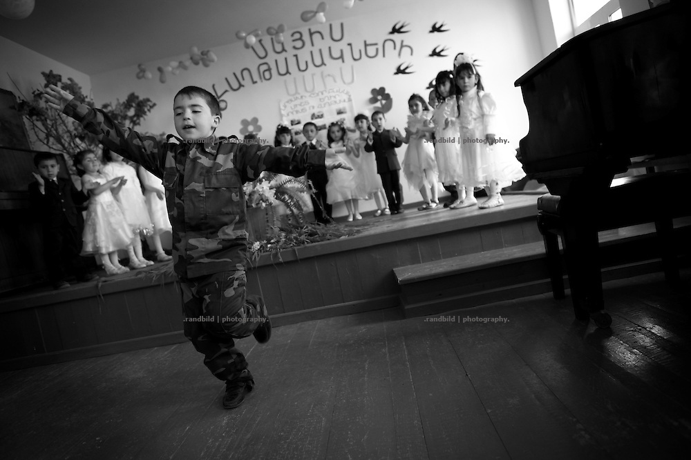 "A little boy dressed in camouflage performs for pupils parents and officials to celebrate Shushis liberation.This image is part of the photoproject ""The Twentieth Spring"", a portrait of caucasian town Shushi 20 years after its so called ""Liberation"" by armenian fighters. In its more than two centuries old history Shushi was ruled by different powers like armeniens, persians, russian or aseris. In 1991 a fierce battle for Karabakhs independence from Azerbaijan began. During the breakdown of Sowjet Union armenians didn´t want to stay within the Republic of Azerbaijan anymore. 1992 armenians manage to takeover ""ancient armenian Shushi"" and pushed out remained aseris forces which had operate a rocket base there. Since then Shushi became an ""armenian town"" again. Today, 20 yeras after statement of Karabakhs independence Shushi tries to find it´s opportunities for it´s future. The less populated town is still affected by devastation and ruins by it´s violent history. Life is mostly a daily struggle for the inhabitants to get expenses covered, caused by a lack of jobs and almost no perspective for a sustainable economic development. Shushi depends on donations by diaspora armenians. On the other hand those donations have made it possible to rebuild a cultural centre, recover new asphalt roads and other infrastructure. 20 years after Shushis fall into armenian hands Babies get born and people won´t never be under aseris rule again. The bloody early 1990´s civil war has moved into the trenches of the frontline 20 kilometer away from Shushi where it stuck since 1994. The karabakh conflict is still not solved and could turn to an open war every day. Nonetheless life goes on on the south caucasian rocky tip above mountainious region of Karabakh where Shushi enthrones ever since centuries."