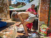 04 AUGUST 2015 - BUNGAMATI, NEPAL: A woman bathes her husband in a small Internal Displaced Persons settlement in the town square in Bungamati, a village about an hour from Kathmandu. Three months after the earthquake many families still live in tents and temporary shelters scattered around the village. The Nepal Earthquake on April 25, 2015, (also known as the Gorkha earthquake) killed more than 9,000 people and injured more than 23,000. It had a magnitude of 7.8. The epicenter was east of the district of Lamjung, and its hypocenter was at a depth of approximately 15 km (9.3 mi). It was the worst natural disaster to strike Nepal since the 1934 Nepal–Bihar earthquake. The earthquake triggered an avalanche on Mount Everest, killing at least 19. The earthquake also set off an avalanche in the Langtang valley, where 250 people were reported missing. Hundreds of thousands of people were made homeless with entire villages flattened across many districts of the country. Centuries-old buildings were destroyed at UNESCO World Heritage sites in the Kathmandu Valley, including some at the Kathmandu Durbar Square, the Patan Durbar Squar, the Bhaktapur Durbar Square, the Changu Narayan Temple and the Swayambhunath Stupa. Geophysicists and other experts had warned for decades that Nepal was vulnerable to a deadly earthquake, particularly because of its geology, urbanization, and architecture.    PHOTO BY JACK KURTZ