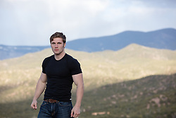 All American man outdoors overlooking a mountain range at sunset
