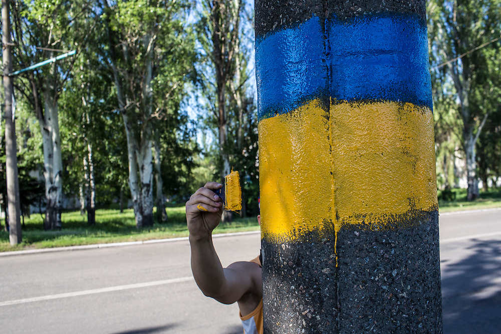 DOBROPILLYA, UKRAINE - MAY 21:  Tagir, who declined to give his last name, paints the colors of the Ukrainian flag on a light pole on May 21, 2014 in Dobropillya, Ukraine. Days before presidential elections are scheduled, questions remain whether the eastern regions of Donetsk and Luhansk are stable enough to administer the vote. (Photo by Brendan Hoffman/Getty Images) *** Local Caption ***
