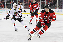 Mar 27; Newark, NJ, USA; New Jersey Devils defenseman Marek Zidlicky (2) skates with the puck while being defended by Chicago Blackhawks center Dave Bolland (36) during the first period at the Prudential Center.