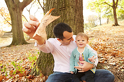 Lifestyle photograph of happy baby girl with father in park during fall season
