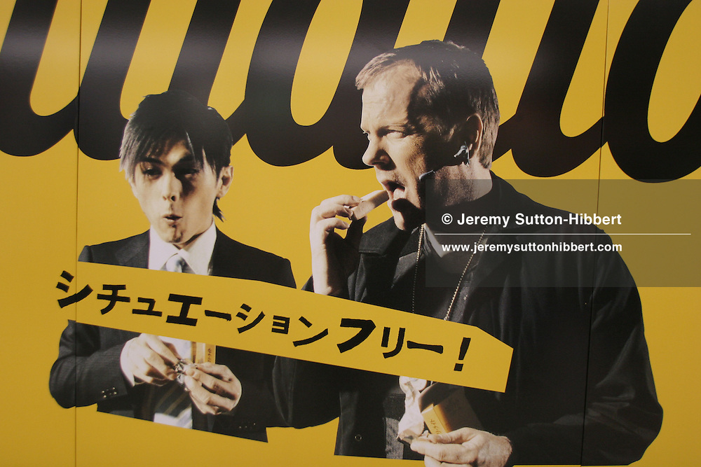 """KIEFER SUTHERLAND IN BISCUIT ADVERTISEMENT, TOKYO, JAPAN. A Japanese woman in kimono walks past a poster in the underground station depicting American actor, and star of '24', Kiefer Sutherland, advertising 'Calorie Mate' -a Japanese nutritional biscuit snack bar, in Tokyo, Japan, Monday, Oct. 9, 2006.  The Japanese text on the poster reads """"Situation free"""", implying the snack bar can be eaten anywhere, anytime, any situation."""
