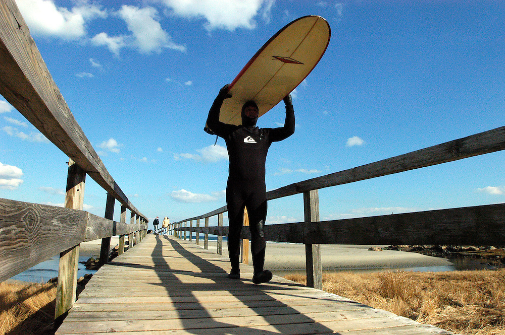 """Gloucester: Todd Bleckley of Malden carries his surf board on his head while crossing the footbridge at Good Harbor Beach Tuesday. Bleckley and his fiancee, Heidi O'Brien, both tested the waters but said the conditions were rougher than they expected so they were packing it in for the day. The trip wasn't a waste though, said Bleckley. """"A bad day surfing is better than no surfing at all."""" .Photo by Mike Dean/Gloucester Daily Times Tuesday, February 19, 2008"""