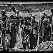"""In this """"Signature Series"""" images by David Longstreath, mourners gather outside Kabul, Afghanistan in September 2002, to bury a young man killed the day before in a car bombing. At least 21 others died when a car bomb as set off in a busy market area of downtown Kabul. The man was the sole support for his family."""