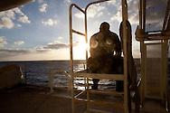 HM3 Edgar Camacho looks out at the ocean during a break on board the USNS Comfort, a naval hospital ship, before its mission to help survivors of the earthquake in Haiti on Monday, January 18, 2010 in the Atlantic Ocean off the coast of the United States.